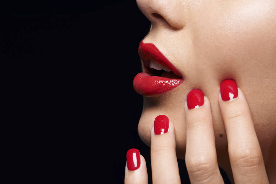 A cropped studio shot of a beautiful model wearing red lipstick and nailpolish